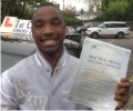 Aaron with Driving test pass certificate